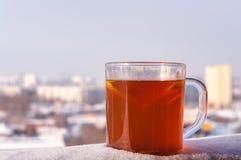 Tasse transparente avec la boisson, le citron et l'orange épicés chauds sur le fond de la ville d'hiver Photo stock