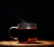 Tasse transparente en verre de thé chaud sur un fond noir image libre de droits