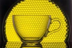 tasse transparente sur un fond de nid d'abeilles jaune pour la photographie image stock