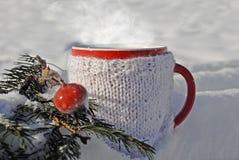 Tasse tricotée de boisson chaude à l'arrière-plan d'hiver Image stock