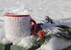 Tasse tricotée de boisson chaude à l'arrière-plan d'hiver Images libres de droits