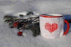 Tasse tricotée de boisson chaude à l'arrière-plan d'hiver Images stock