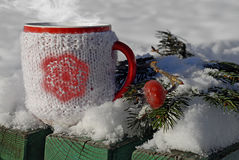 Tasse tricotée de boisson chaude à l'arrière-plan d'hiver Photographie stock