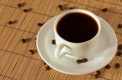 Tasse und Untertasse des weißen Kaffees auf der Tabelle lizenzfreie stockfotografie