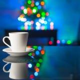 Tasse und Untertasse des weißen Kaffees auf einem Glastisch auf dem Hintergrund bunten bokeh Lizenzfreies Stockbild
