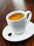 Tasse und Untertasse des weißen Kaffees mit einzelner Bohne Lizenzfreie Stockfotos