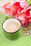 Tasse verte de café sur le fond dépouillé Photo stock