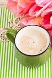 Tasse verte de café sur le fond dépouillé Images stock