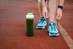 Tasse verte et femme de smoothie de detox laçant les chaussures de course avant W photos libres de droits
