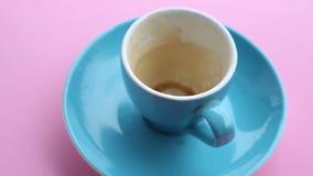 Tasse vide bleue avec le reste de café de plat tournant rose banque de vidéos