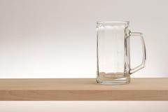 Tasse vide de bière blonde sur un conseil en bois image stock