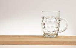 Tasse vide de bière blonde sur un conseil en bois photos stock