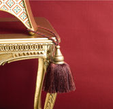 Tassel and golden chair on red background Stock Images