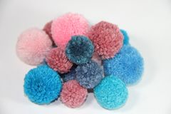 Blue and pink wool pompoms. Tassels and pompoms wool handicrafts bijouterie  pearls Royalty Free Stock Photo