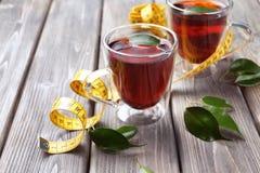 Tassen Tee und messendes Band auf Holztisch Stockbild