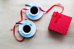 Tasses avec du café, boîte-cadeau décoré par le ruban sur la table Photos libres de droits
