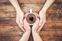 Tasses avec du café dans les mains des hommes et des femmes Images stock