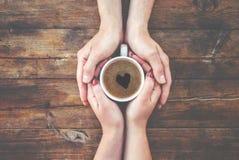 Tasses avec du café dans les mains des hommes et des femmes Photographie stock libre de droits