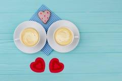 Tasses blanches avec des coeurs de cappuccino et de rouge Photographie stock libre de droits