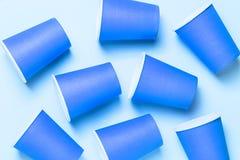 Tasses bleues en plastique sur le fond rose Concept de pollution d'environnement Configuration plate Vue supérieure photos libres de droits