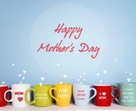 Tasses colorées avec des messages pour la maman sur un fond bleu Photo stock