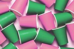 Tasses colorées en plastique sur le fond rose Concept de pollution d'environnement Configuration plate Vue supérieure image stock