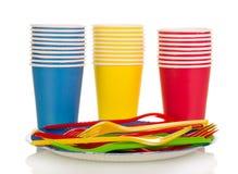 Tasses colorées et fourchettes en plastique d'isolement sur le blanc Image stock