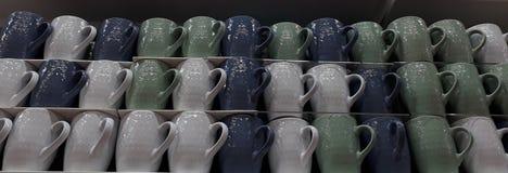 Tasses colorées sur l'étagère dans le magasin Image libre de droits