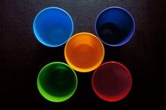 Tasses colorées sur la table noire Images libres de droits