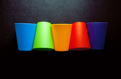 Tasses colorées sur la table noire Photographie stock libre de droits