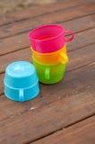 Tasses colorées sur le fond en bois Image stock