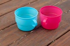 Tasses colorées sur le fond en bois Photos stock
