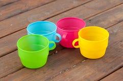 Tasses colorées sur le fond en bois Photographie stock