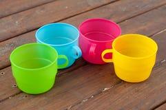 Tasses colorées sur le fond en bois Photo libre de droits