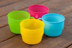 Tasses colorées sur le fond en bois Images stock