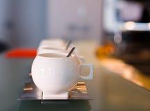 Tasses contemporaines de porcelaine blanche avec les soucoupes a en acier inoxydable Photo libre de droits