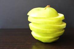 Tasses coupées juteuses fraîches vert pomme sur un fond noir photo stock