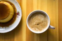 Tasses d'un blanc avec du café régénérateur d'arome sur une table de cuisine, Photo stock