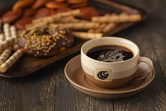 Tasses de butées toriques de thé et de chocolat sur un fond noir photo stock