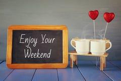 Tasses de café à côté de tableau noir avec le texte : APPRÉCIEZ VOTRE WEEK-END photographie stock libre de droits