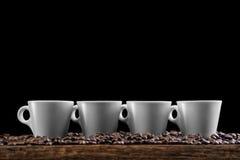 Tasses de café avec des grains de café d'isolement sur le fond noir, photographie de produit pour le café Photos libres de droits