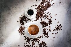 Tasses de café avec des grains de café, lumière du soleil sur un fond de marbre Photos stock