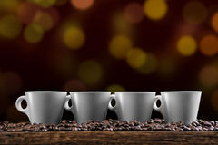 Tasses de café avec des grains de café sur le fond d'or, photographie de produit pour le café Image stock