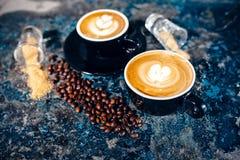 Tasses de café avec l'art de latte Café se renversant de barman Photographie stock libre de droits