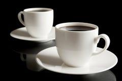 Tasses de café avec la soucoupe d'isolement sur le noir Photo libre de droits
