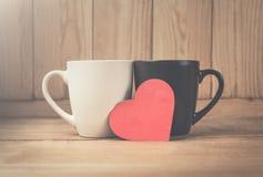 Tasses de café avec le coeur rouge sur un fond en bois Photographie stock