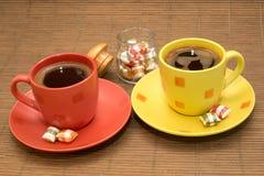 Tasses de café avec les sucreries et le bol en verre colorés entre eux Photos libres de droits
