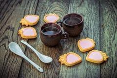 Tasses de café, biscuits crèmes de fraise et cuillères blanches sur une table en bois Photos libres de droits