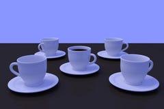 Tasses de café blanc avec la soucoupe sur une surface réfléchie foncée Photographie stock