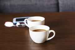 Tasses de café chaud sur la table et les verres en bois Images libres de droits